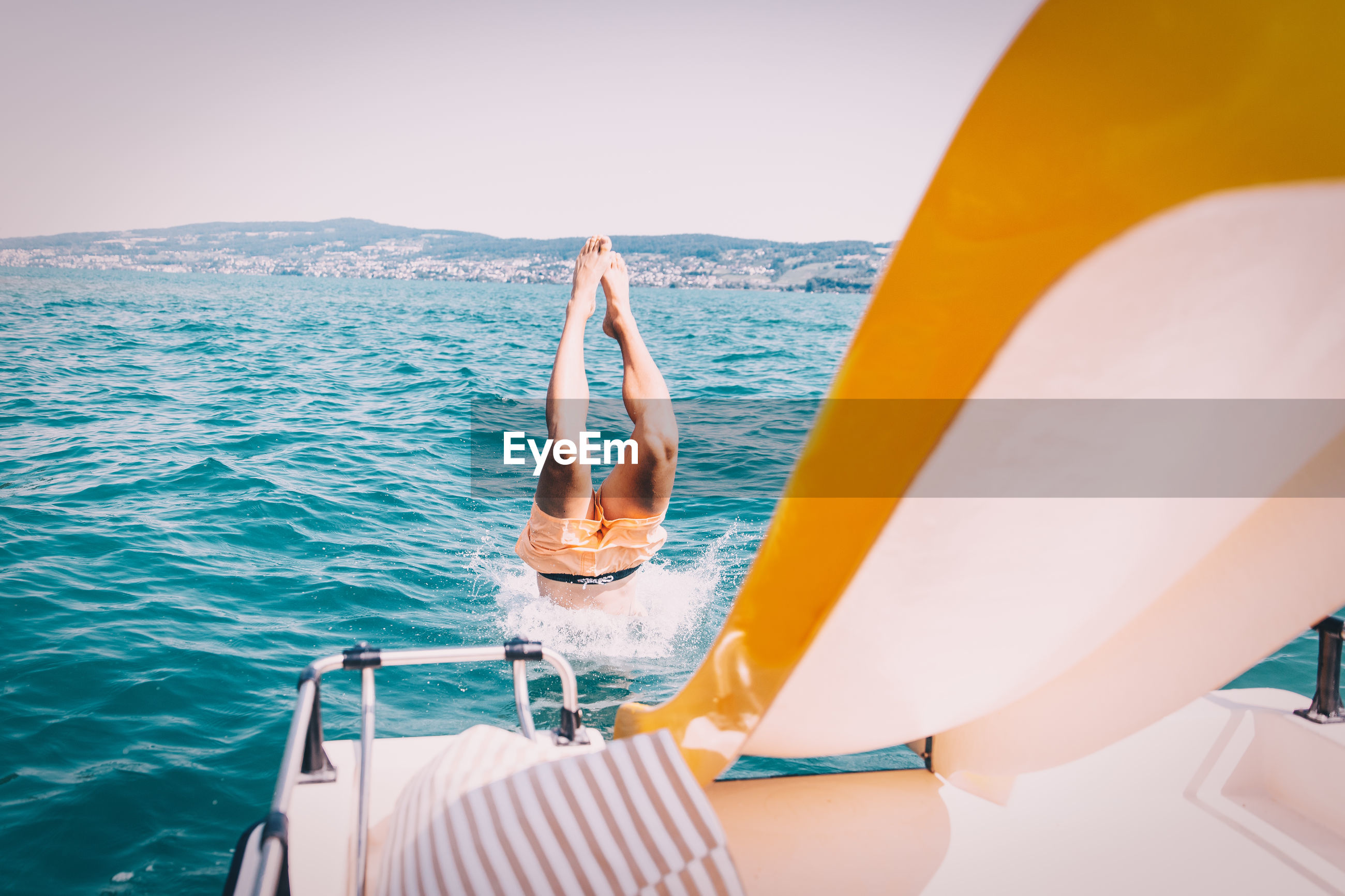 Low section of woman in boat sailing on sea against clear sky