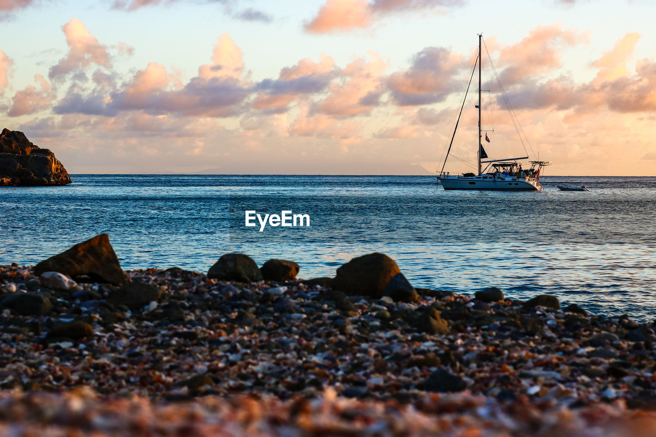 sky, water, sea, transportation, cloud - sky, nautical vessel, mode of transportation, beauty in nature, scenics - nature, rock, horizon, solid, tranquility, sunset, land, horizon over water, tranquil scene, nature, beach, sailboat, no people, outdoors, pebble