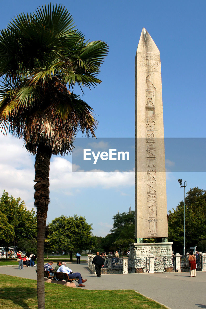 tree, plant, sky, nature, architecture, palm tree, day, travel destinations, travel, tropical climate, tourism, group of people, memorial, built structure, incidental people, men, real people, outdoors, tall - high, large group of people, architectural column