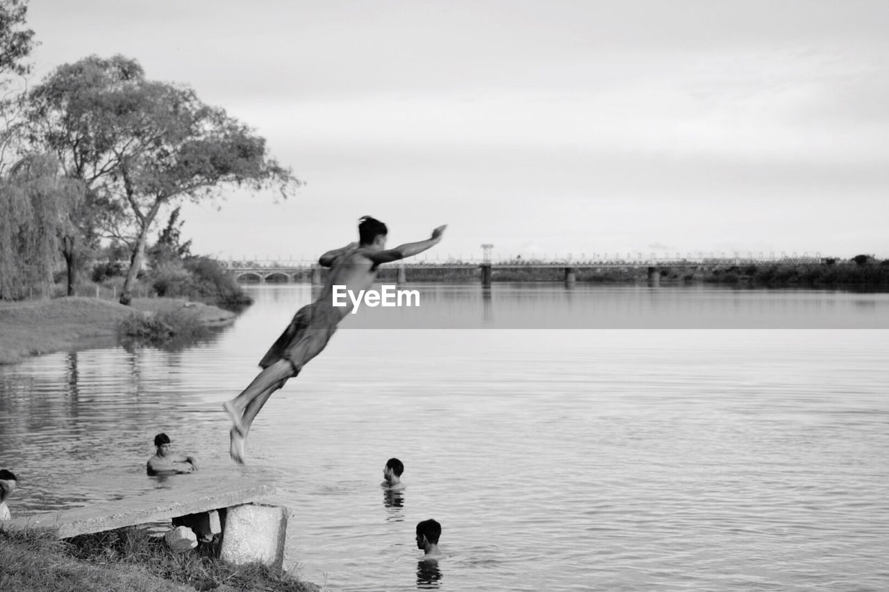 water, lake, real people, day, outdoors, nature, tree, upside down, swimming, animal themes, sky, leisure activity, one person, full length, beauty in nature, young adult