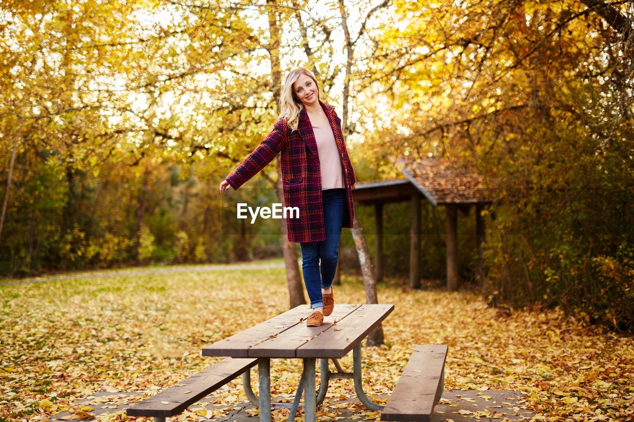 autumn, leaf, full length, plant part, tree, one person, standing, casual clothing, nature, change, blond hair, hair, plant, day, young adult, leisure activity, women, park - man made space, portrait, outdoors, hairstyle, jeans, scarf