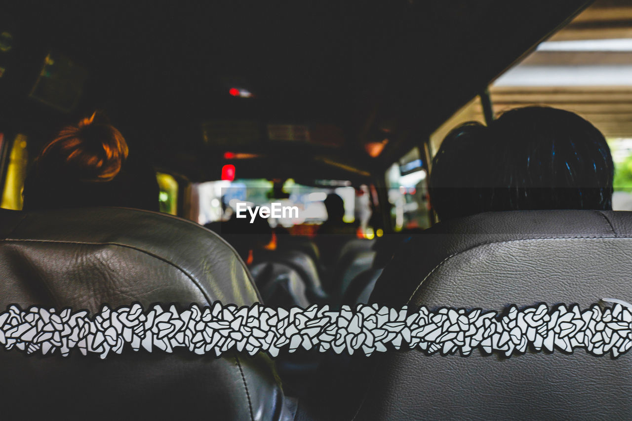 mode of transportation, seat, vehicle interior, transportation, land vehicle, real people, vehicle seat, indoors, motor vehicle, focus on foreground, travel, car, car interior, relaxation, rear view, lifestyles, sitting, one person, public transportation, incidental people