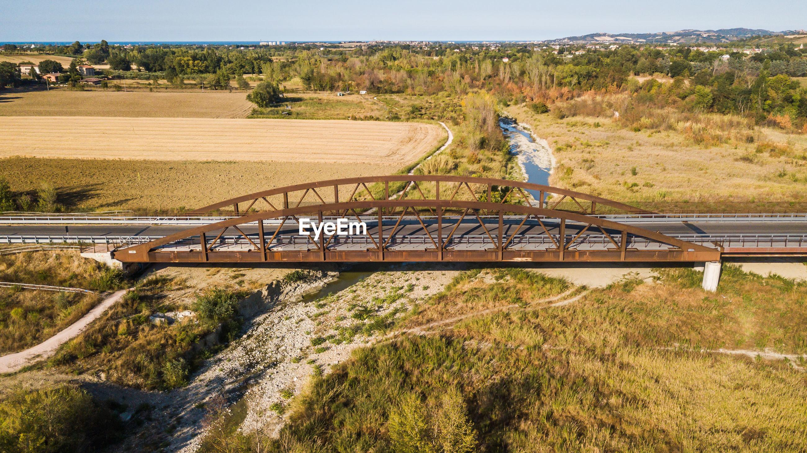 Bridge over field against trees