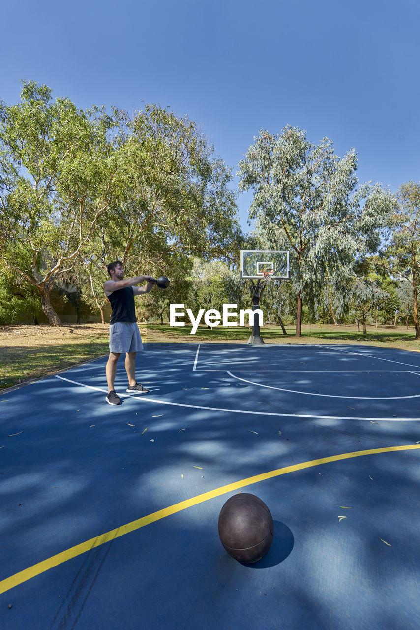 Young Man Exercising With Kettlebell On Basketball Court At Park