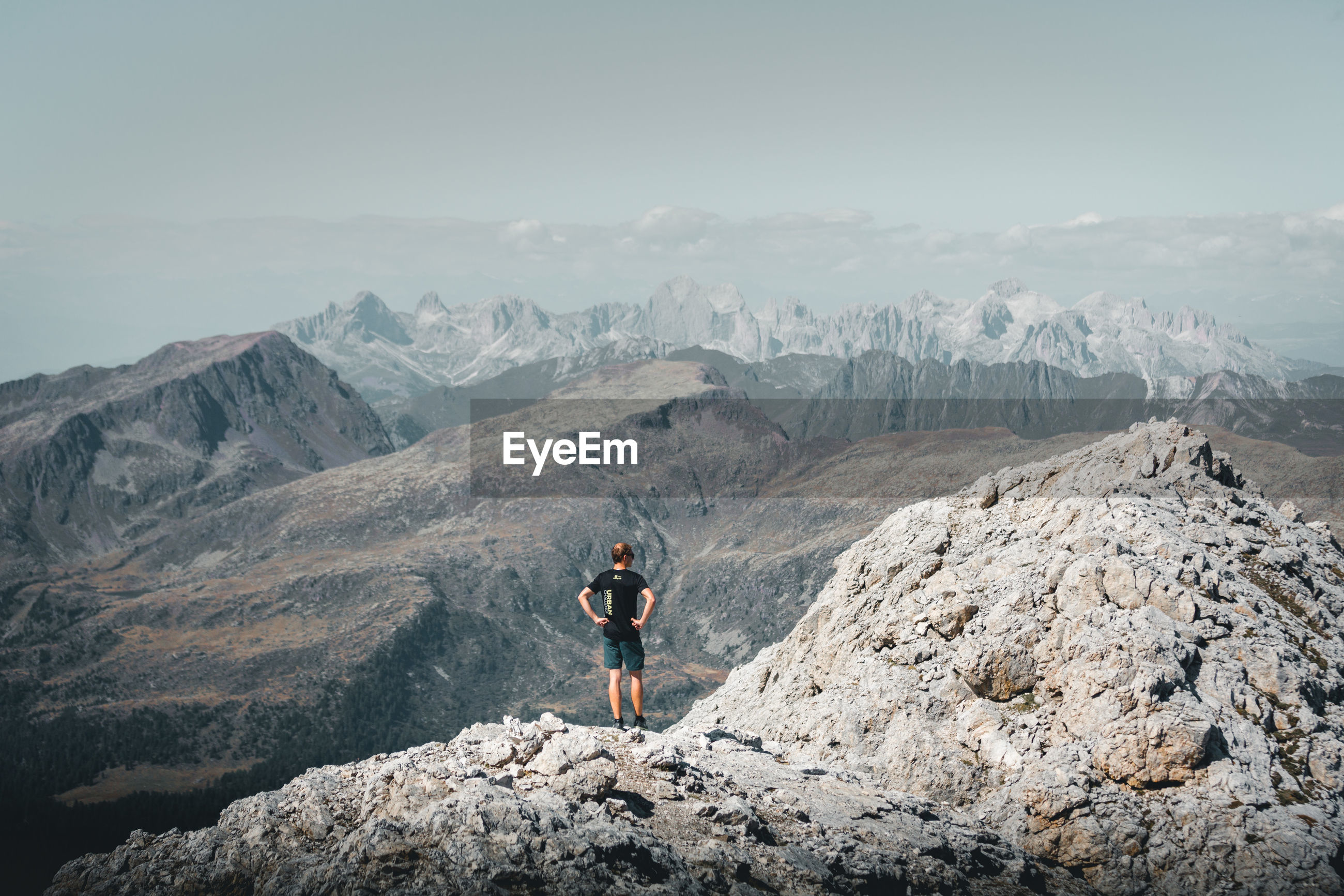 MAN STANDING ON ROCK LOOKING AT MOUNTAINS