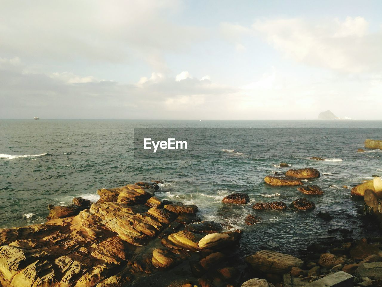 sea, water, horizon over water, scenics, nature, tranquility, sky, tranquil scene, beauty in nature, no people, outdoors, rock - object, day, cloud - sky, beach