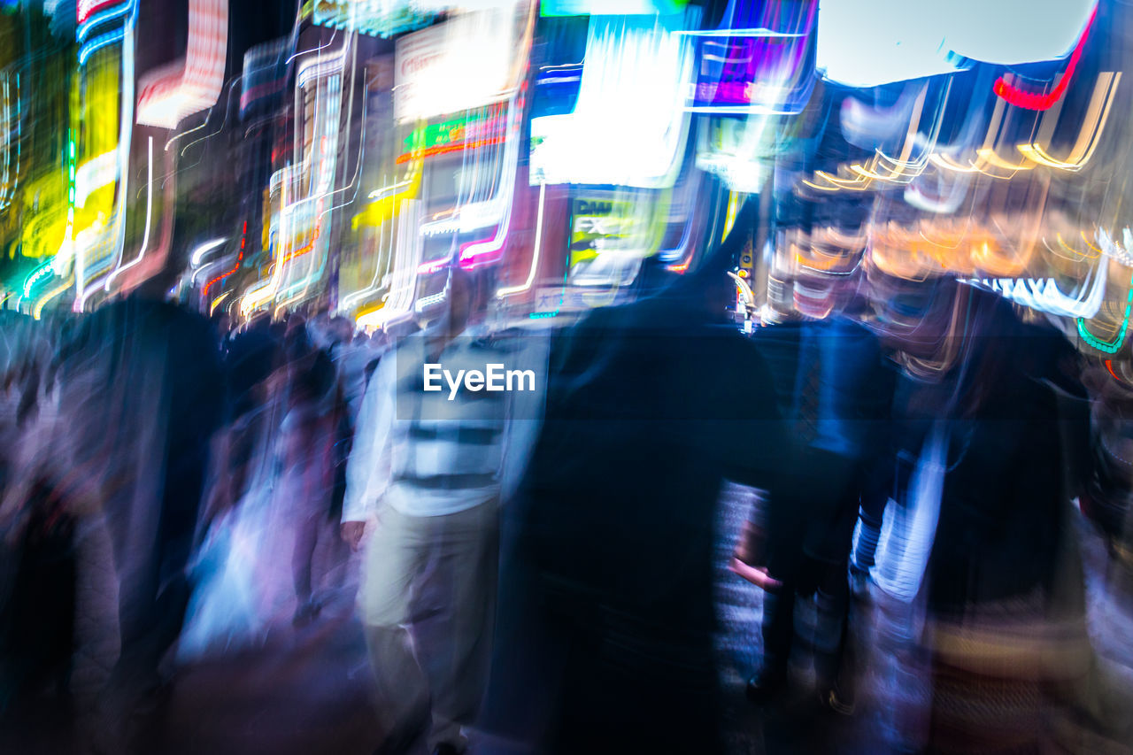 Blurred motion of people on street at night