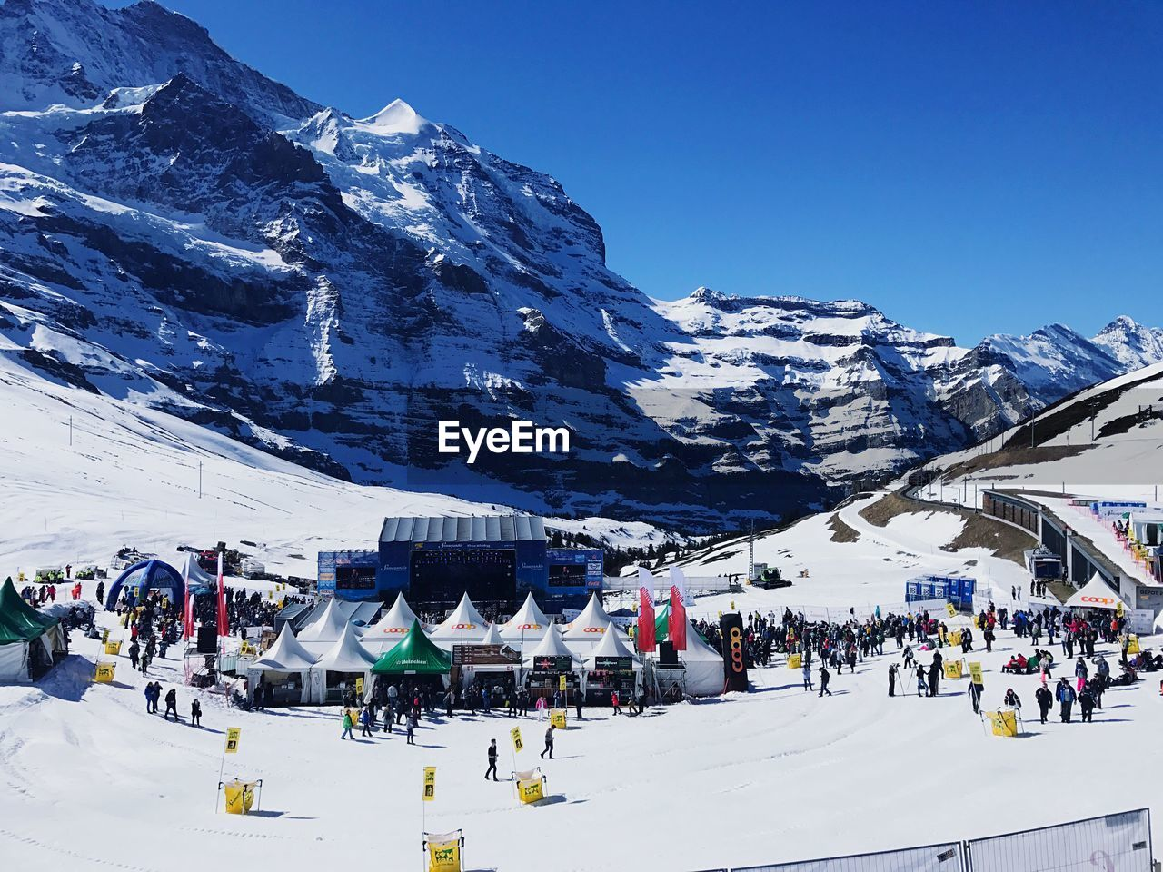 PANORAMIC VIEW OF PEOPLE ON SNOW COVERED MOUNTAIN