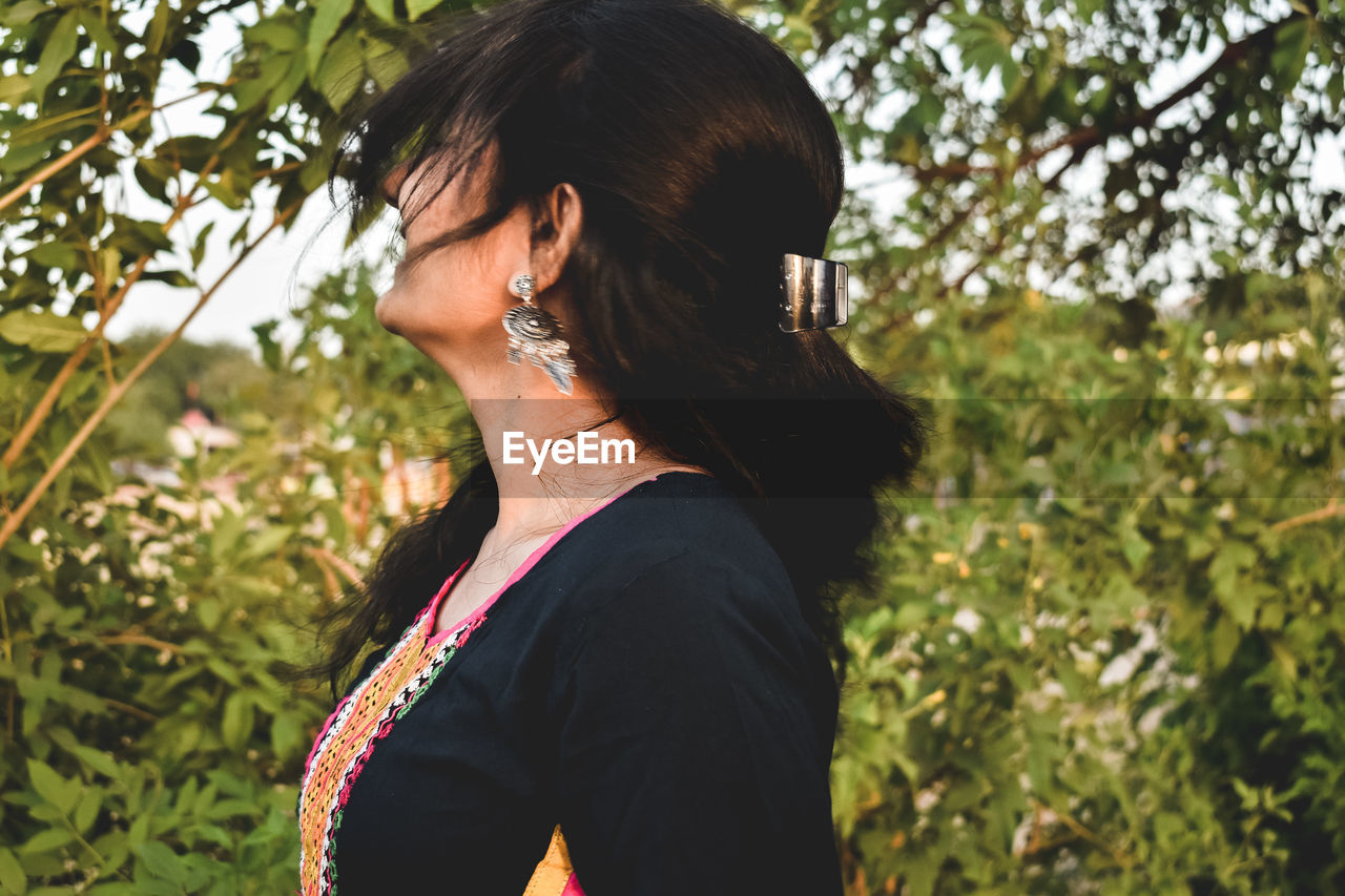real people, plant, one person, lifestyles, leisure activity, hairstyle, women, young adult, adult, young women, nature, hair, focus on foreground, tree, headshot, casual clothing, day, standing, jewelry, outdoors