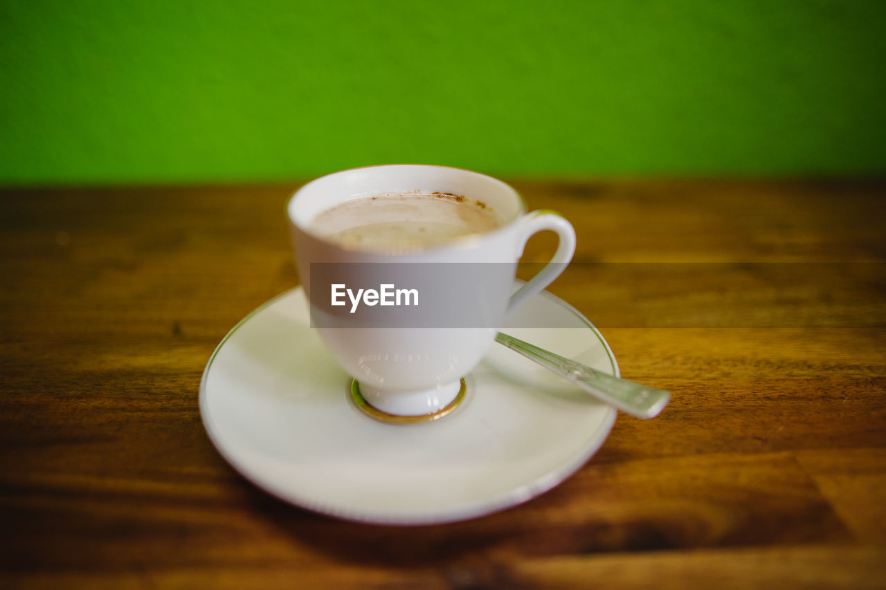 table, coffee, spoon, eating utensil, saucer, crockery, food and drink, drink, kitchen utensil, still life, coffee cup, cup, mug, coffee - drink, indoors, wood - material, refreshment, close-up, no people, white color, frothy drink, temptation, latte, non-alcoholic beverage