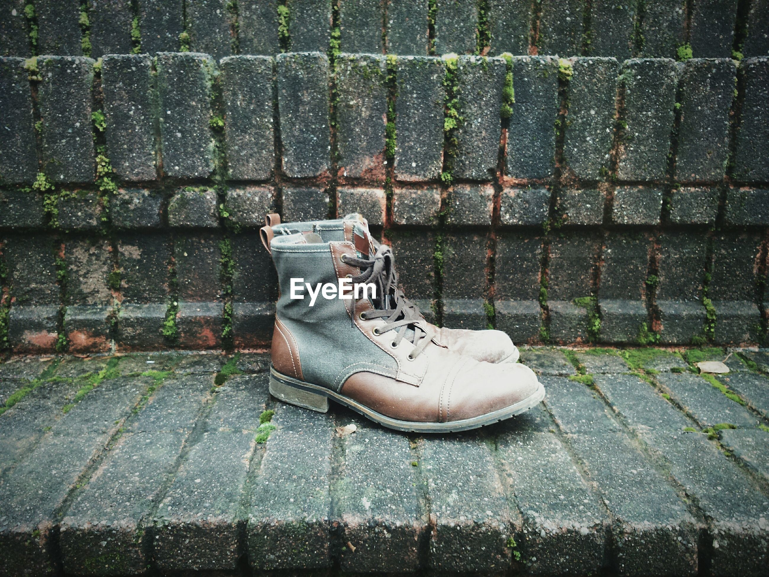shoe, high angle view, relaxation, footwear, cobblestone, paving stone, sitting, pair, outdoors, day, sidewalk, footpath, lying down, resting, street, brick wall, flooring, low section, no people, wall - building feature