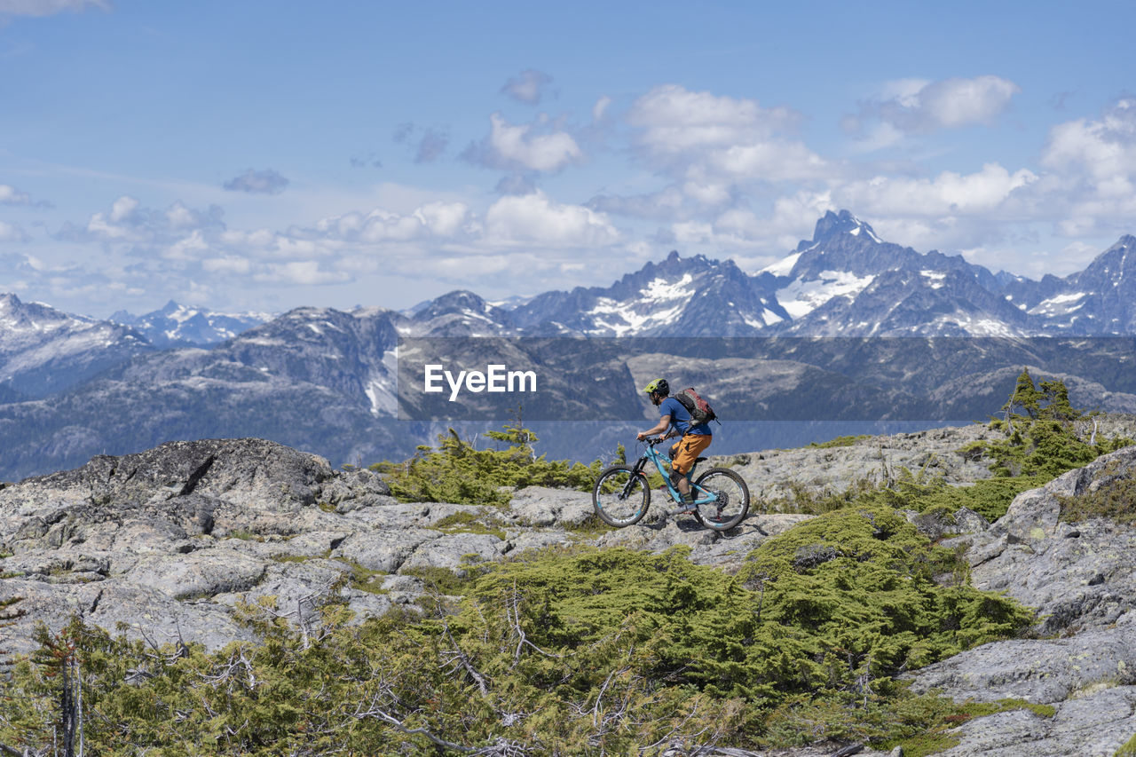 mountain, mountain range, one person, leisure activity, adventure, nature, real people, lifestyles, transportation, beauty in nature, sky, bicycle, activity, cloud - sky, scenics - nature, day, sport, riding, ride, skill, outdoors