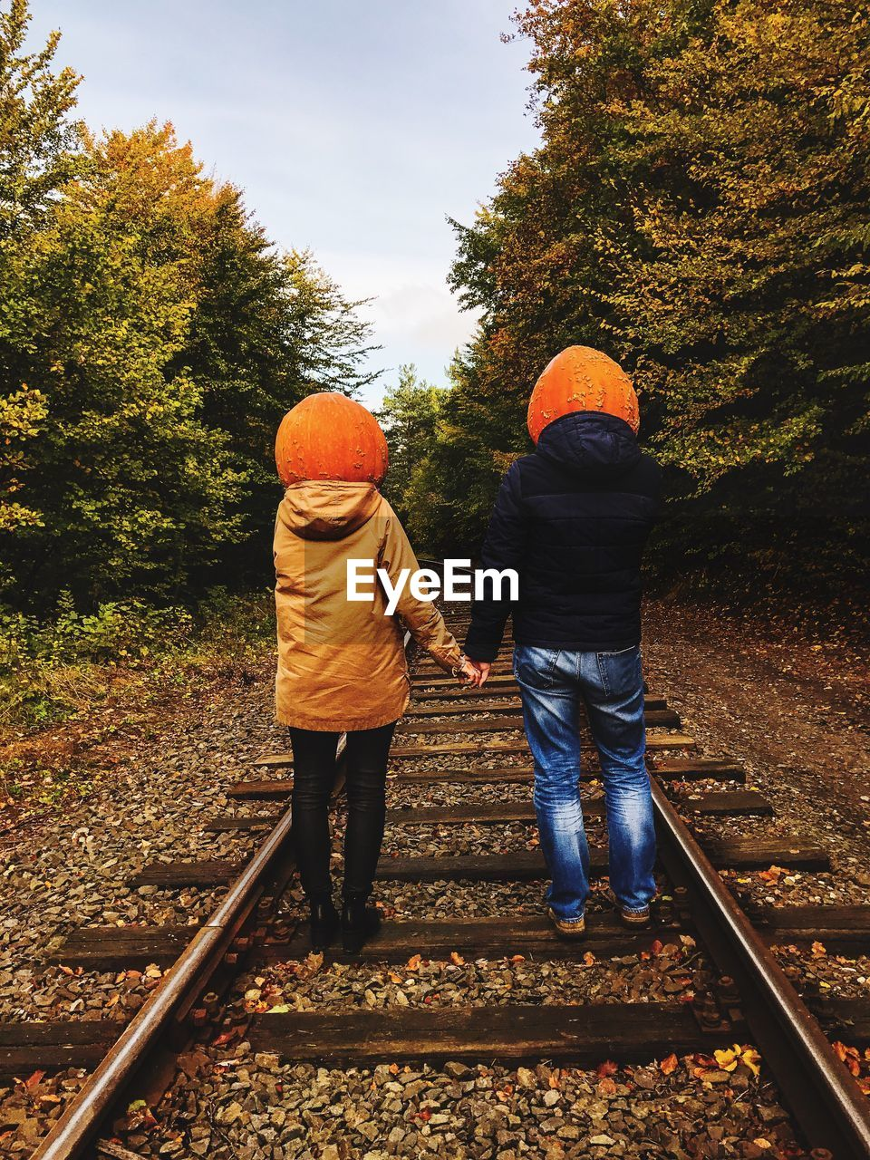 Rear View Of Couple With Pumpkin Head Standing At Railroad Track During Autumn