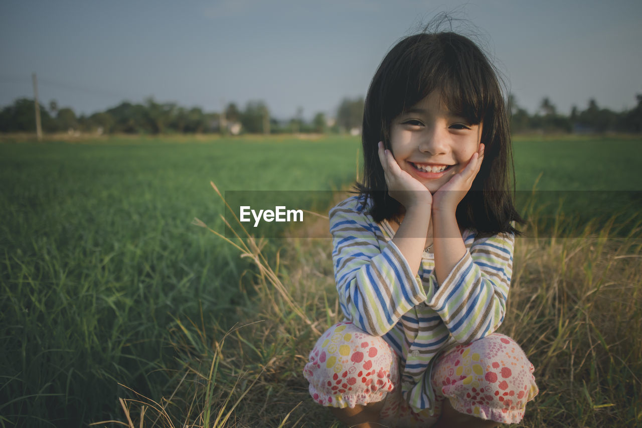 Portrait of cute girl crouching on grassy field against sky