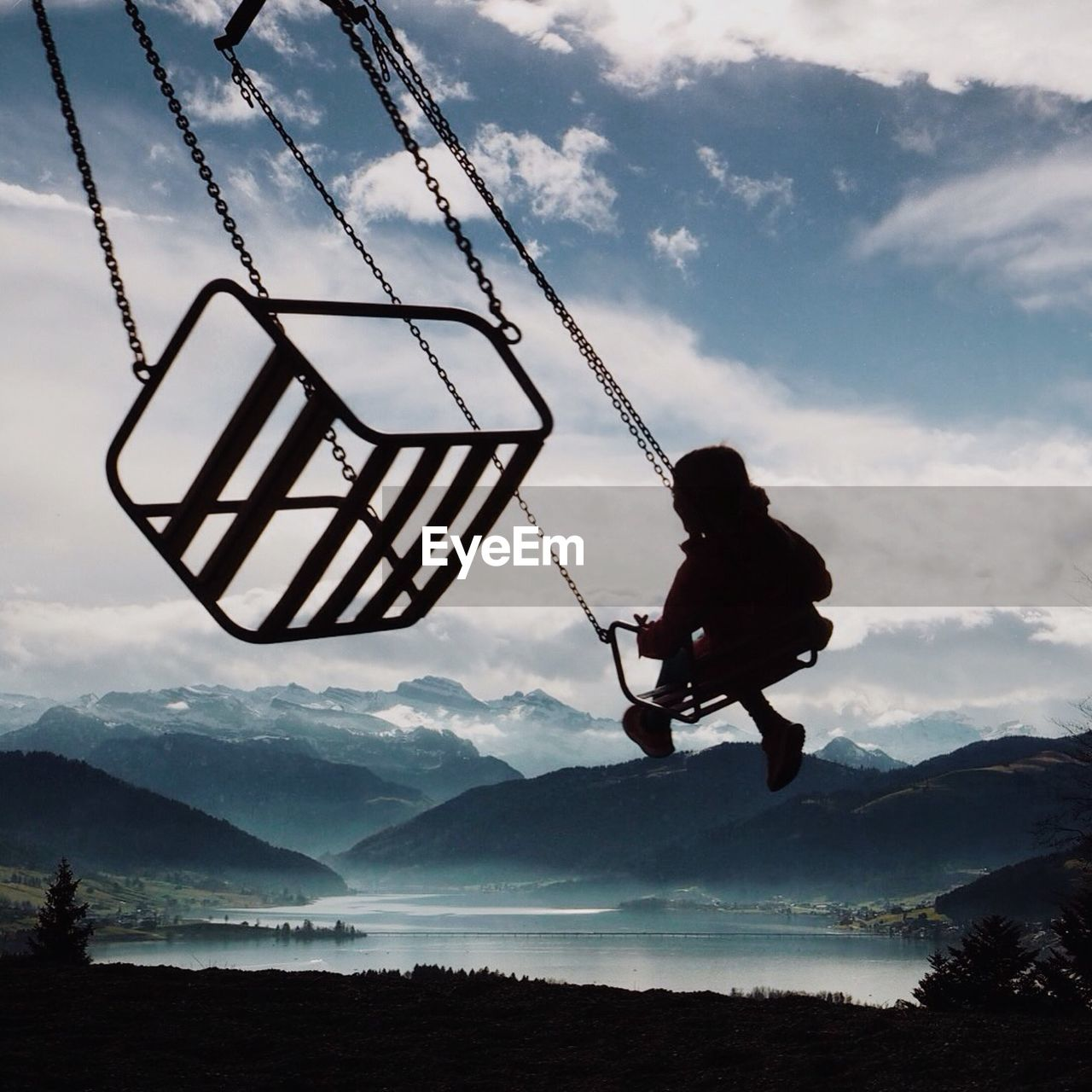 Child enjoying in chain swing ride in front of lake and mountains against cloudy sky