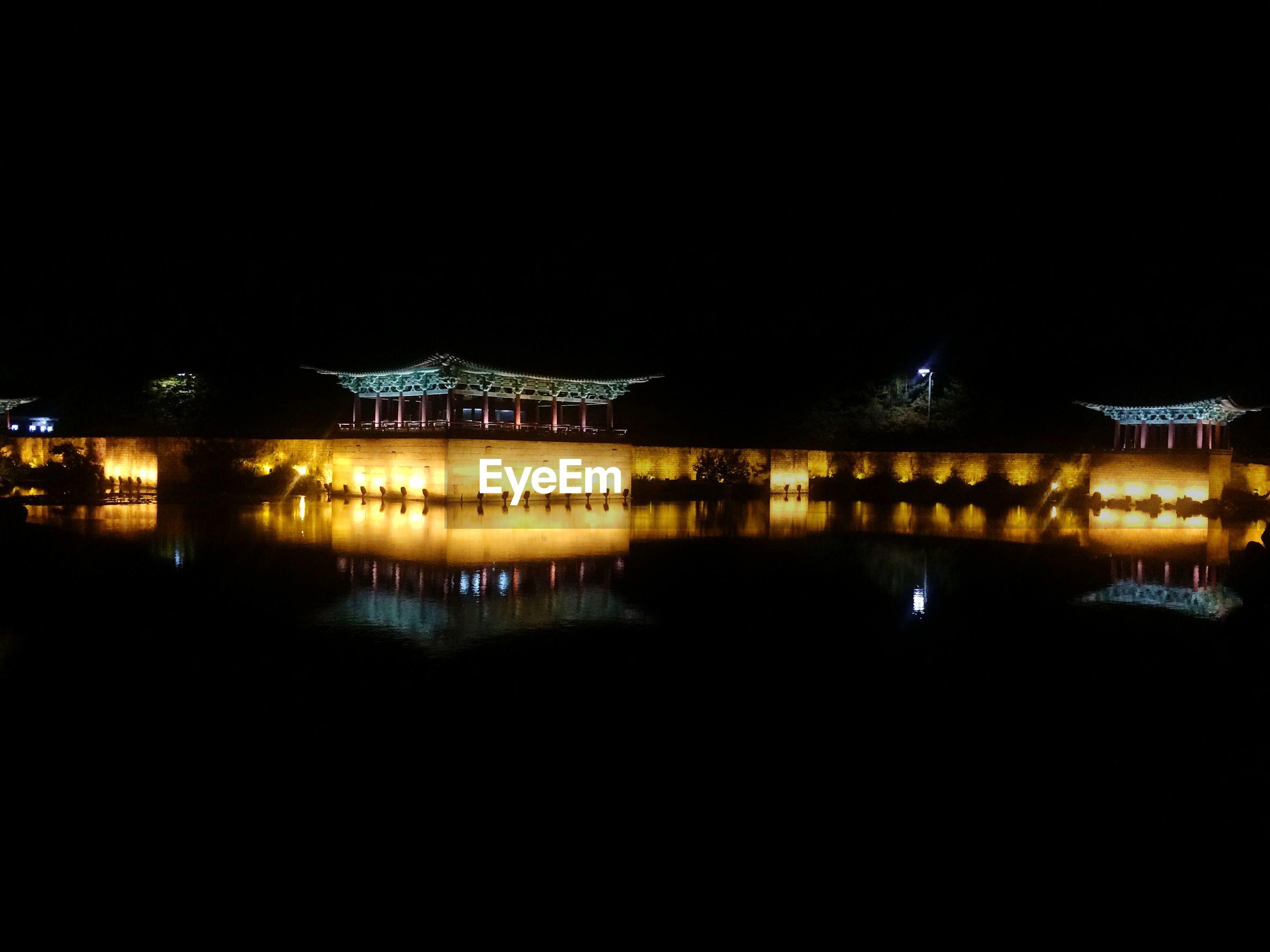 Reflection of illuminated traditional building on lake at night