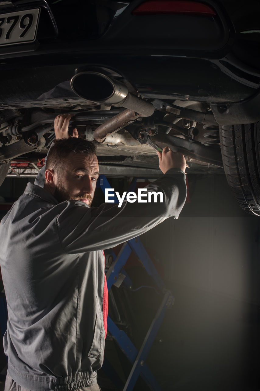 Portrait of male mechanic repairing car at auto repair shop