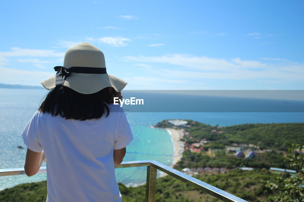 sky, sea, rear view, one person, real people, standing, nature, lifestyles, leisure activity, water, hat, scenics - nature, day, horizon, beauty in nature, adult, railing, women, casual clothing, horizon over water, outdoors, looking at view, hairstyle