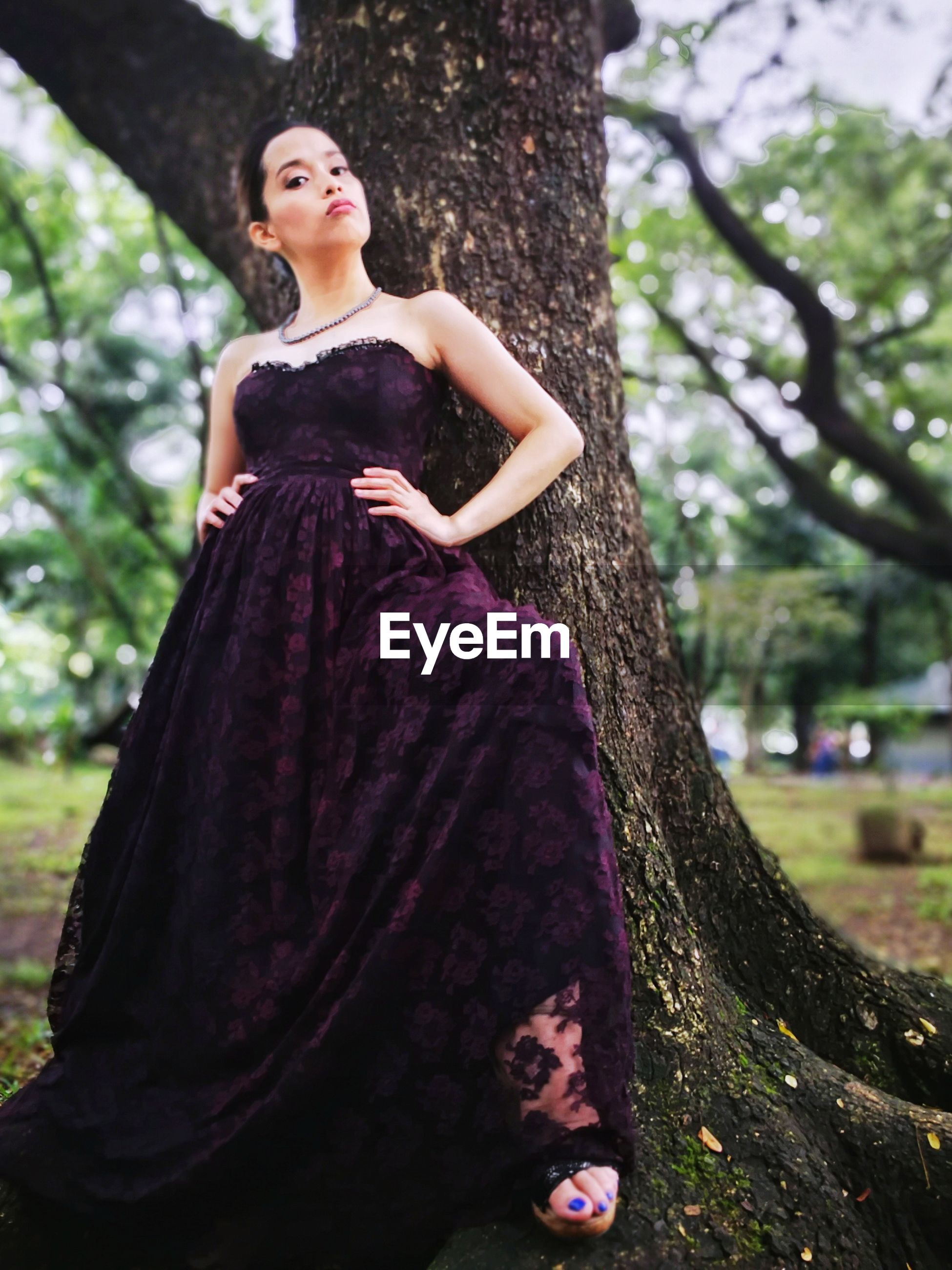 Full length portrait of young woman wearing evening gown standing against tree at park