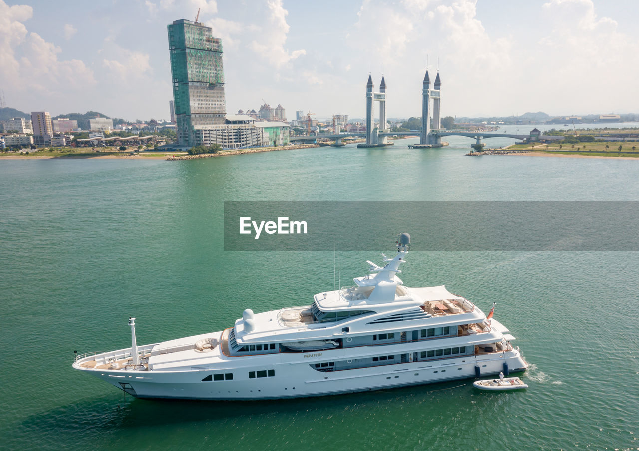 water, transportation, nautical vessel, mode of transportation, architecture, built structure, building exterior, sky, sea, nature, city, waterfront, no people, travel, day, outdoors, cloud - sky, building, luxury, yacht, skyscraper, office building exterior, cruise ship, cityscape, passenger craft