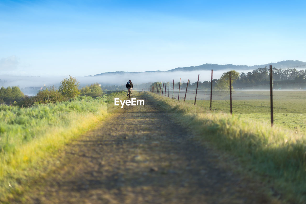 Man Cycling On Dirt Road Passing Through Landscape