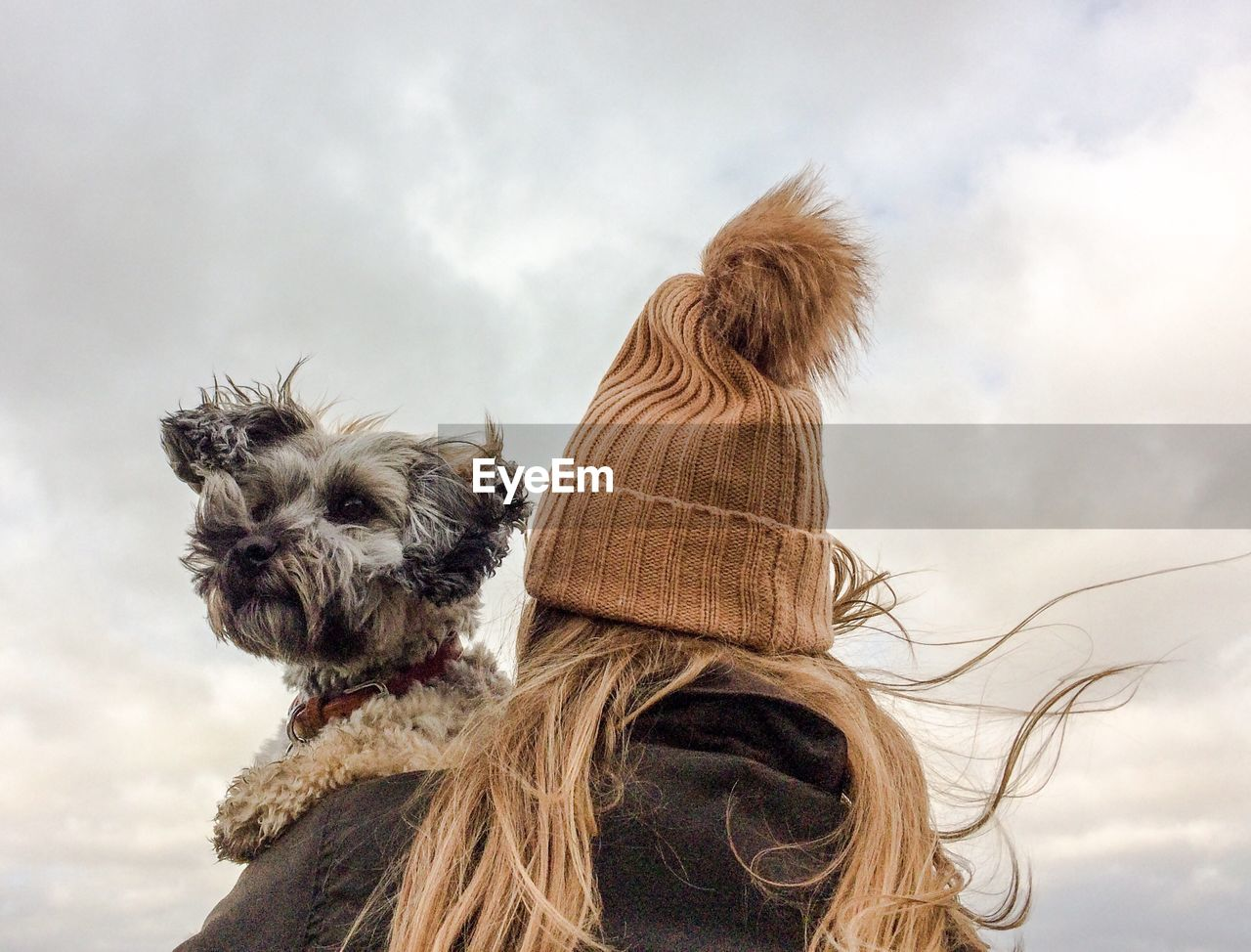 Low Angle View Of Woman With Dog Against Sky