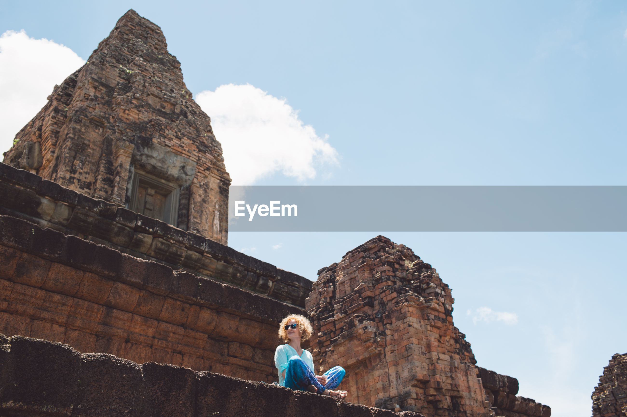 Low angle view of woman sitting on historic building against sky