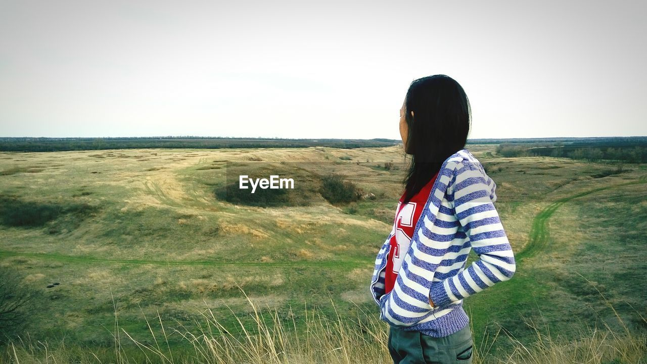 Side View Of Woman Looking At Green Landscape Against Clear Sky