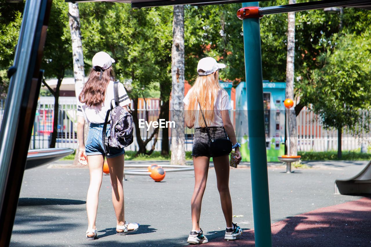 full length, two people, hat, real people, adult, city, rear view, women, walking, tree, casual clothing, clothing, day, people, fashion, plant, architecture, leisure activity, lifestyles, togetherness, outdoors, hairstyle, shorts