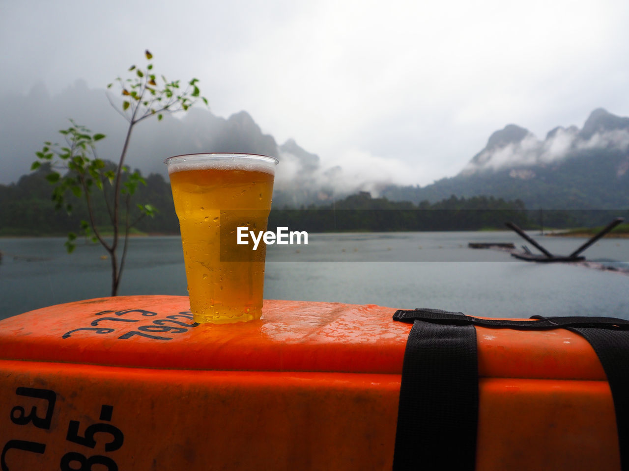 Close-up of beer on container by lake