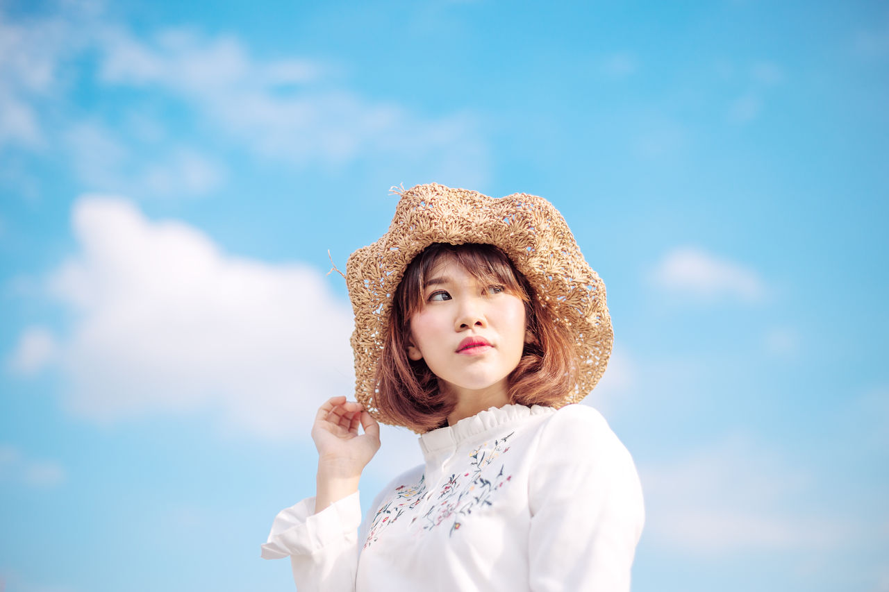 Low Angle View Of Woman In Sun Hat Against Sky