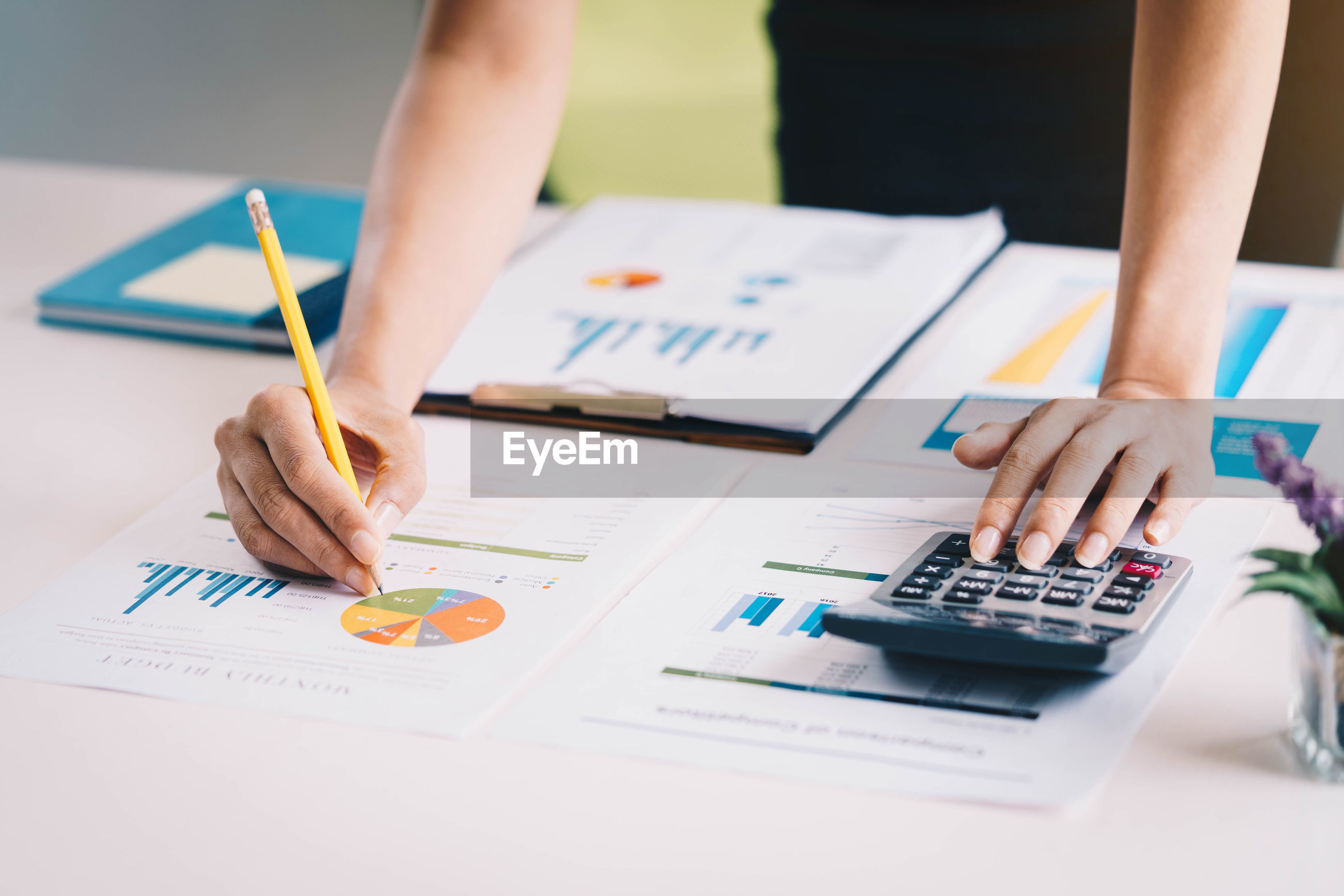 Midsection of businesswoman writing on graph at desk in office