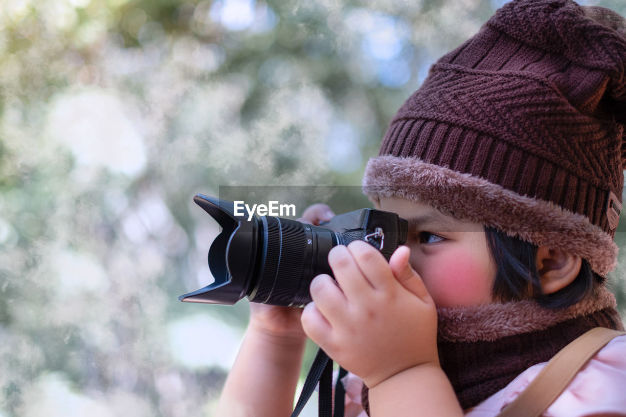 Portrait of a cute little girl in wool hat taking a picture with camera at weather is cold