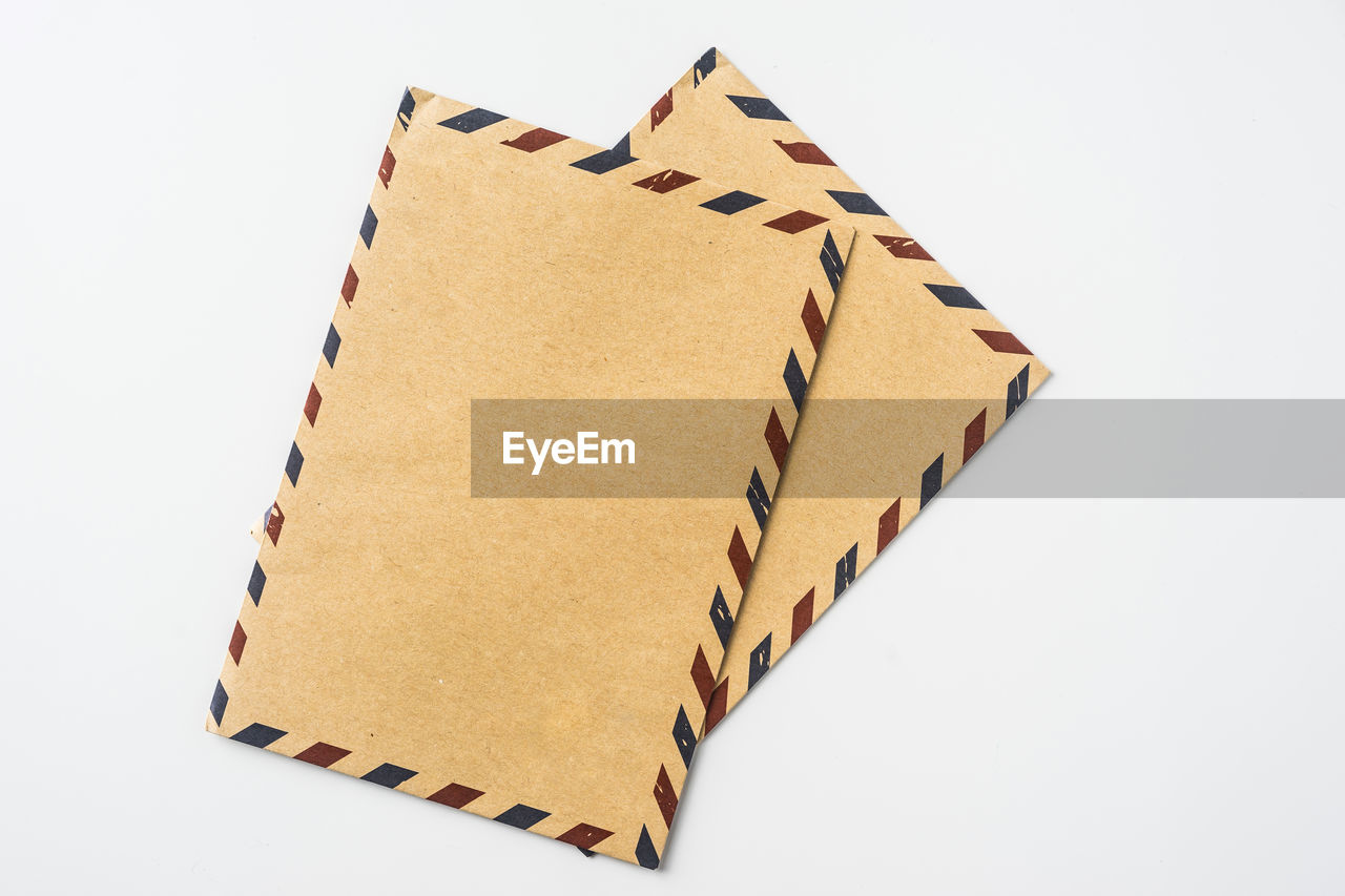 Directly above view of blank envelopes against white background