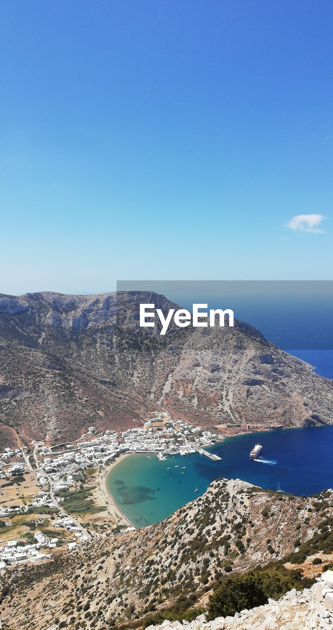 HIGH ANGLE VIEW OF SEA AND MOUNTAINS AGAINST BLUE SKY