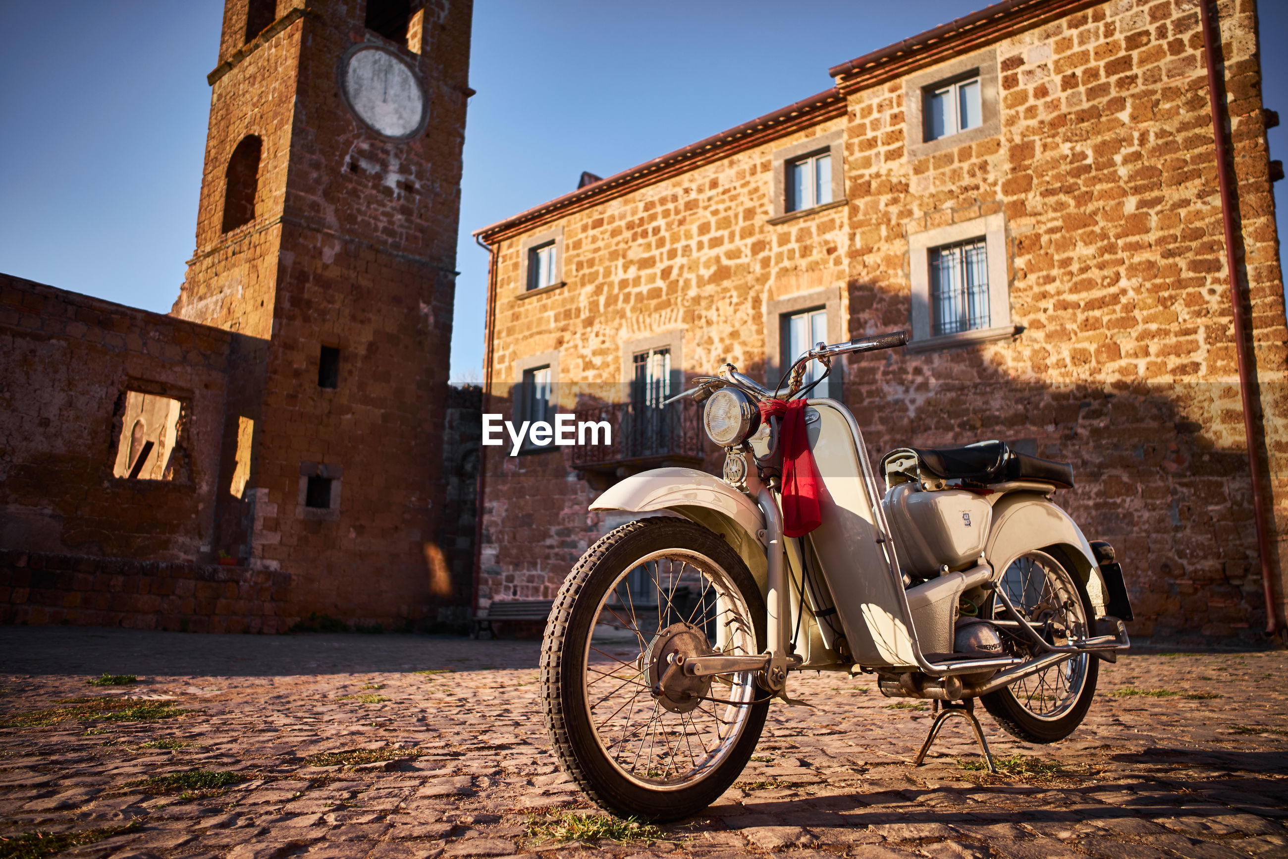 Vintage motorcycle in ghost town celleno in viterbo, sunset on the village
