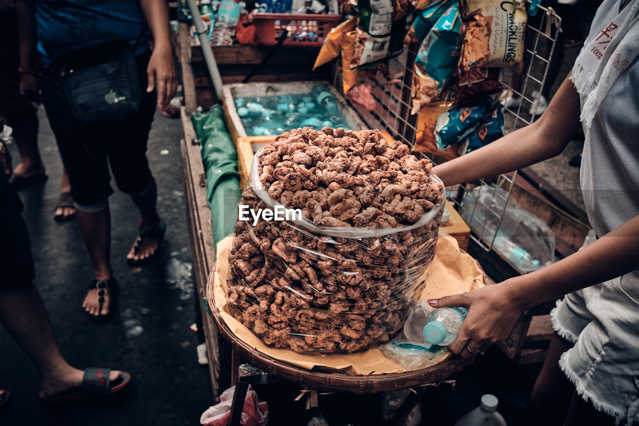 HIGH ANGLE VIEW OF PEOPLE FOR SALE AT MARKET