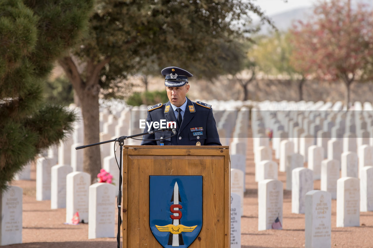 day, government, focus on foreground, one person, military, clothing, cemetery, front view, grave, real people, uniform, tree, outdoors, standing, safety, security, protection, three quarter length