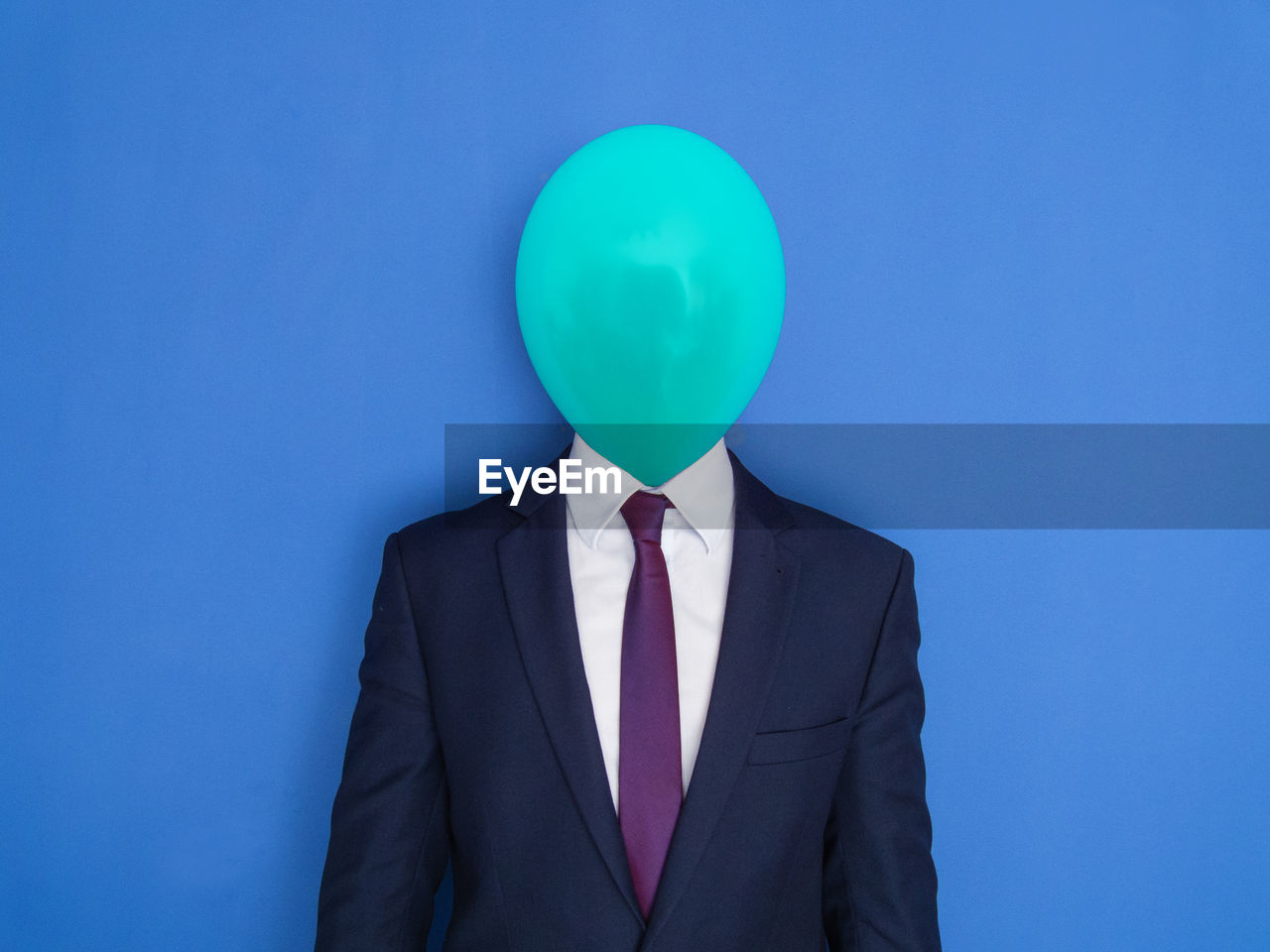 Face of businessman covered with balloon standing against blue background