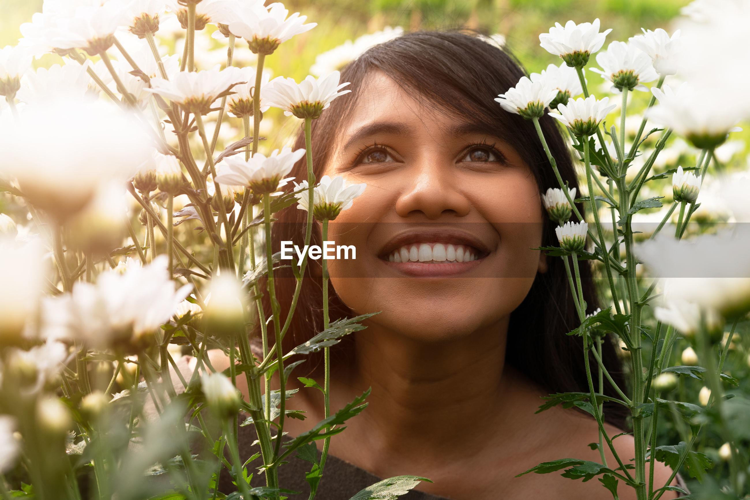 Smiling woman against blooming flowers
