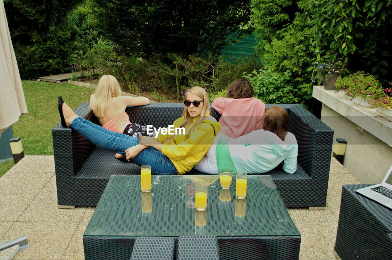 High angle view of friends with juice on table relaxing in yard