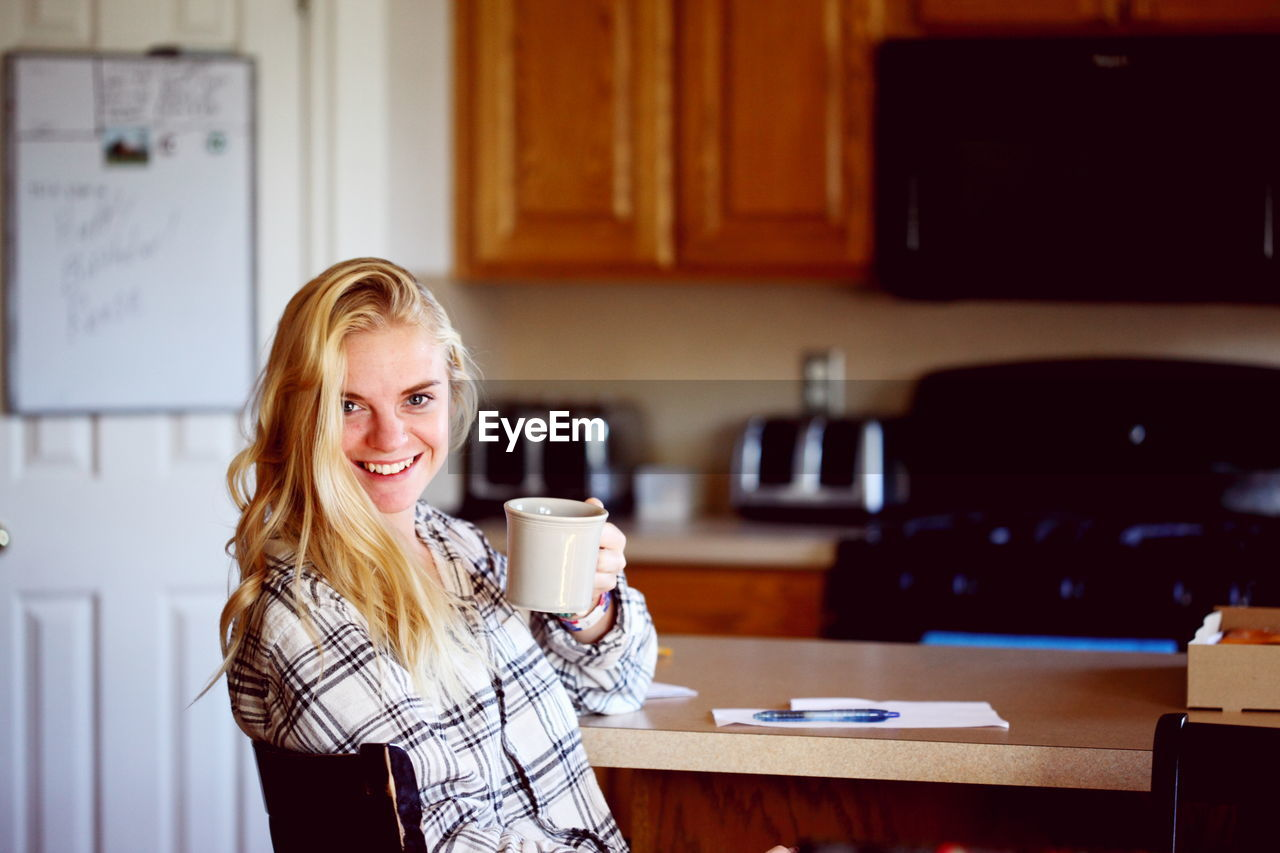 Portrait Of Smiling Young Woman Having Coffee By Table In Kitchen At Home