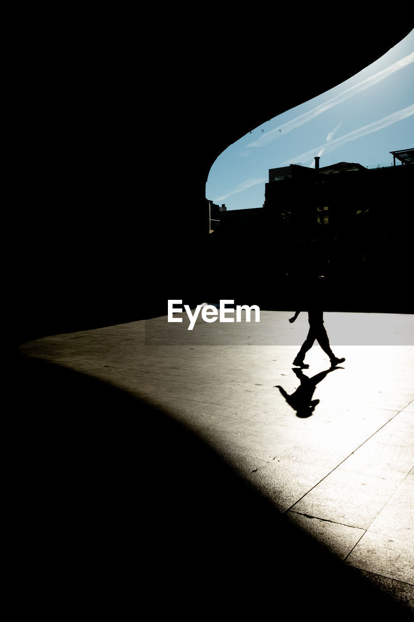 silhouette, one person, shadow, real people, sunlight, lifestyles, full length, architecture, nature, mode of transportation, transportation, leisure activity, walking, built structure, men, sky, copy space, city, day, outdoors, dark