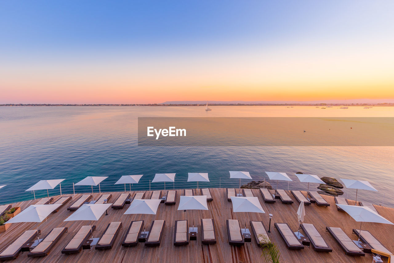 sky, sunset, water, scenics - nature, beauty in nature, nature, sea, no people, tranquil scene, wood - material, idyllic, tranquility, horizon over water, horizon, orange color, outdoors, in a row, architecture, high angle view