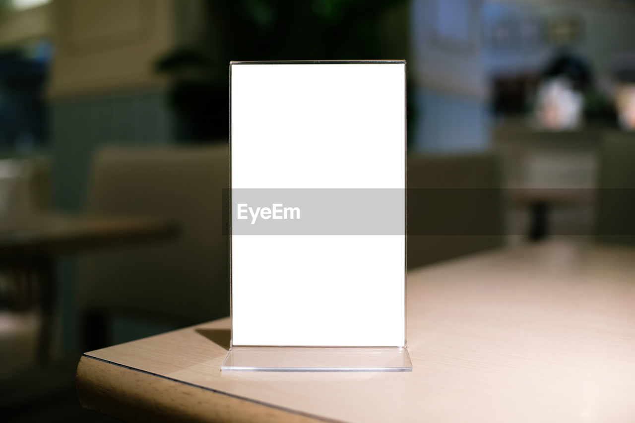 white color, table, focus on foreground, indoors, blank, close-up, paper, no people, wood - material, lighting equipment, illuminated, art and craft, copy space, technology, communication, still life, shape, creativity, container, empty