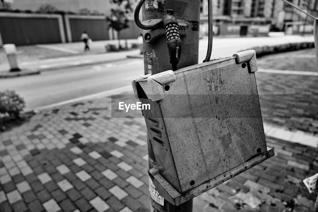focus on foreground, metal, day, street, city, footpath, outdoors, safety, security, no people, close-up, architecture, protection, sidewalk, nature, built structure, transportation, padlock, lock