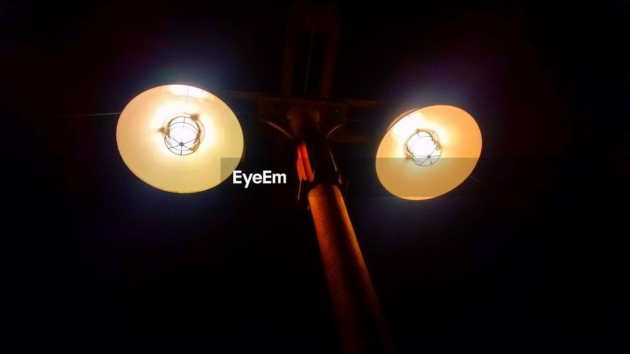 Low angle view of illuminated lamp post at night