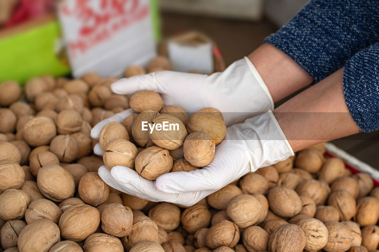 Close-up of hands in gloves for sale at market stall. buying walnuts
