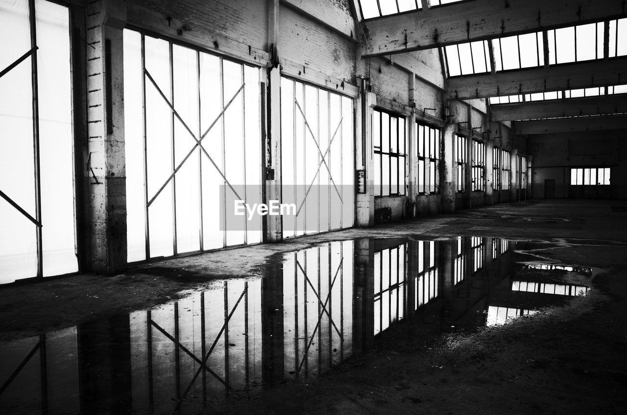 architecture, indoors, built structure, no people, day, abandoned, architectural column, reflection, industry, building, water, absence, warehouse, flooring, empty, domestic room, transportation, window, ceiling, girder