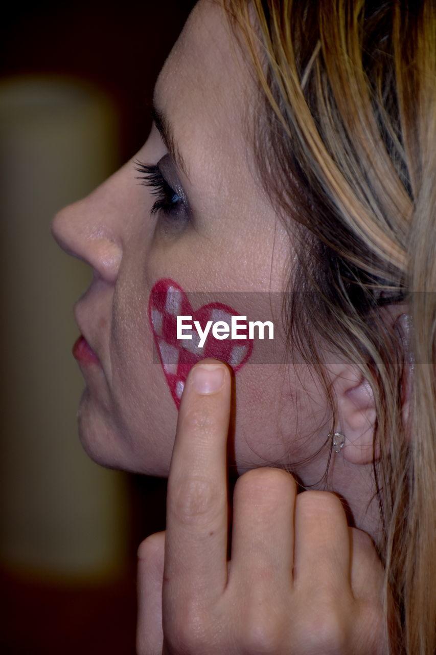 Close-up of woman touching heart shape on cheek
